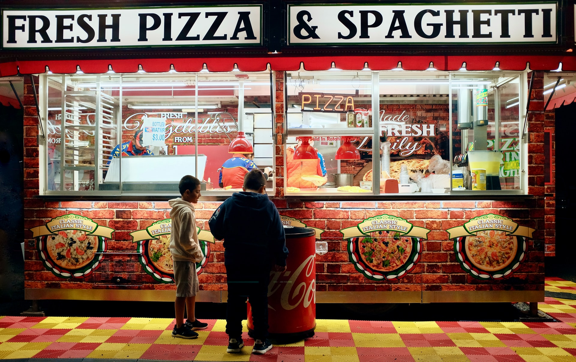 two young boys standing infront of food stall